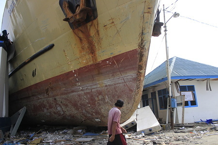 A man seen walking next to a stranded ship at the site where the earthquake happened. A deadly earthquake measuring 7.5 magnitude and a tsunami wave destroyed the city of Palu and much of the area in Central Sulawesi. The death toll was 2088, around 5000 people were seriously injured and some 62,000 people were displaced.
