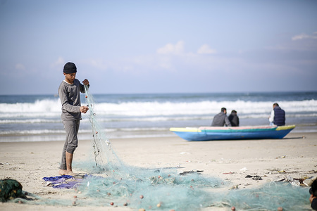 A young Palestinian fisherman seen unravelling a net on the beach in the morning of the last day of the year in Gaza.