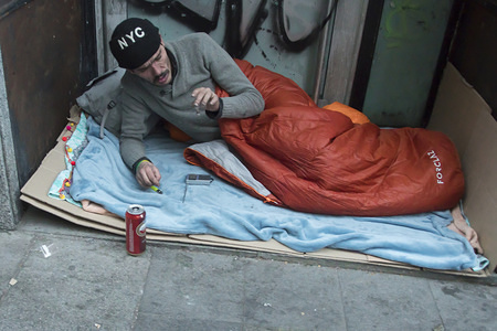 A homeless person seen coughing on the street inside a sleeping bag facing freezing temperatures during the New Year day in the Madrid.