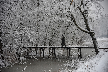 Kashmiri man seen walking on a wooden bridge covered with snow during the fresh snowfall in Srinagar. Snowfall in the Indian side of Kashmir has disrupted air traffic, and road traffic between Srinagar and Jammu, the summer and winter capitals of India's Jammu-Kashmir state, according to news reports.