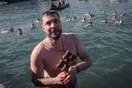 An orthodox believer seen holding a wooden crucifix after catching it during the annual Epiphany Day and the blessing of the waters celebrations in the center of Chania, Greece.