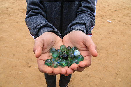 A children seen showing small balls while playing the 'marbles', one of the most popular Palestinian game in the Jabalya refugee camp, Tal al-Zaatar area in the northern Gaza Strip.