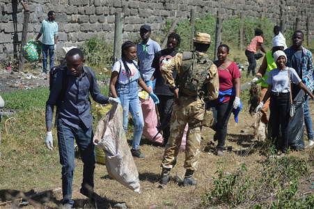 Armed Kenya Wildlife Service game rangers seen watching over a group of students conducting a cleanup exercise during the world wetlands day in Lake Nakuru National Park.The park is a protected wetland of international importance under the Ramsar Convention.