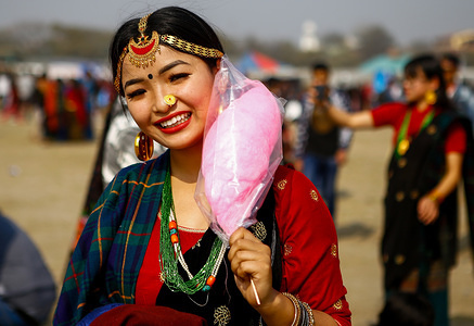A woman from Tamang community dressed in traditional attire poses for a photo as she gather to mark the Sonam Losar or Lunar New Year. Sonam Losar occurs around the same time of year as does Chinese and Mongolian New Year, and it uses the Chinese Calendar as well.