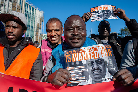 Protesters are seen holding  placards during the demonstration. The coordination committee 'Sudan Unite' in the Netherlands for supporting the Sudanese organized a march to the International Criminal Court situated in The Hague, in solidarity with the revolution in Sudan. People gathered at the Malieveld and from there the demonstration walked to the International Criminal Court. There they demanded the arrest of al-Bashir and all other criminals, force them to stand trial at the ICC, open new investigations into the current crimes against humanity, and stop the deportations of Sudanese in The Netherlands.