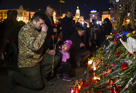 A man seen with his kid paying respects during the event. Ukrainians turn out to pay their respects to the 103 protesters who were killed during the 2014 Ukrainian Revolution in Maidan Square. The majority of the perpetrators of the murders are reported to have been snipers positioned on rooftops around Maidan Square, most of whom have escaped any punishment or justice.