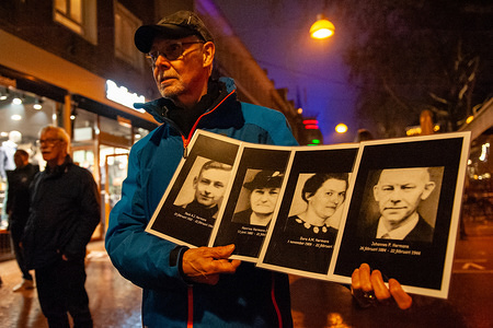 A man is seen holding photos of the  family members that he lost during the bombardment. On February 22nd, 2019 it's 75 years ago that the city center of Nijmegen was destroyed by American bombs, resulting in almost 800 deaths and thousands of injuries. The night before several acts took place along the fire border marked with memorial plaques. More than 40 music groups with 600 to 700 singers, 20 to 25 storytellers and people with torches ran to represent the dreams that Nijmegen had in 1944 on the night before the bombing.