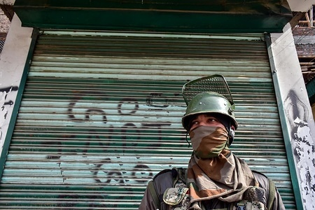 A paramilitary trooper seen standing guard in front of a closed shop with a graffiti during restrictions in Srinagar, Indian Kashmir. Authorities imposed restrictions in parts of the city in view of a strike called by the separatists against the mass detention of over 150 pro-freedom leaders and activists ahead of a hearing at the Supreme Court on Article 35-A, which provides special rights and privileges to the state of Jammu and Kashmir.