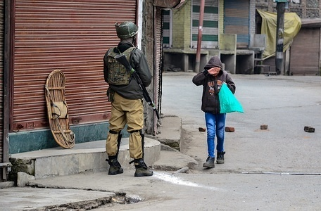 A boy seen hiding his face as he walks past a paramilitary trooper during restrictions in Srinagar, Kashmir. Authorities on imposed restrictions in parts of Srinagar and other parts of south Kashmir to prevent separatist-called protests after the Central government banned Jamaat-e-Islami Jammu and Kashmir for five years, days after arresting its leaders and activists in a massive crackdown.