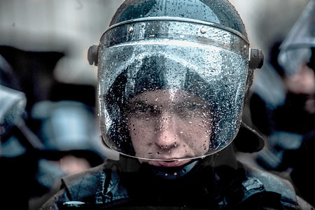 A Police officer seen looking on through his rain spotted face shield during the protest. Thousands of people turned out to protest against corruption within the military and police force under the Presidency of Petro Poroshenko who is up for reflection at the end of March.