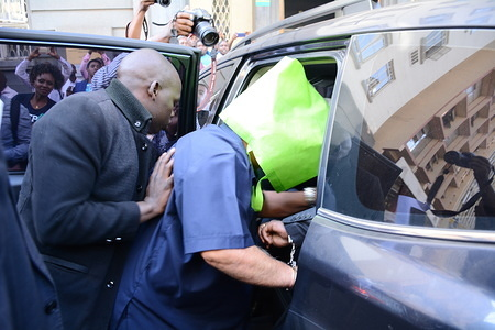 A suspect is seen being taken away by detectives after KSh17 billion currency was discovered in a safe at a Nairobi's Barclay's Bank branch in what was suspected to be a bank fraud.  This comes in the wake of mega corruption scandals involving senior government officials.