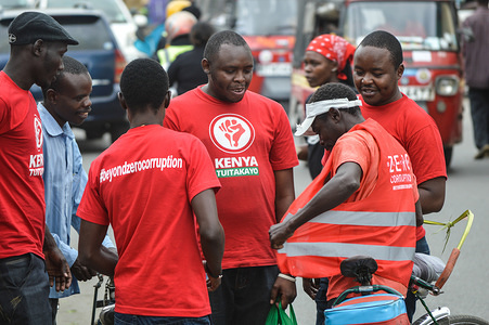 A group of activists allied to  Kenya's Red Vests Movement are seen engaging a member of the public in the streets of Nakuru during the anti-corruption protest Activists allied to Kenya's Red Vests Movement were protesting silently about increased levels of corruption in the government, the activists are demanding action to be taken against all government officials involved in corruption. Kenya loses billions of dollars to corruption in government departments every year and very less action is taken to curb the vice. Every Sunday the activists conduct an anti-corruption protest in churches and streets in different towns of Kenya hoping that the government will get serious on war to corruption.