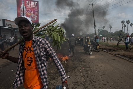 A supporter seen shouting front of burning road barricade during a protest. The welcome rally for returning opposition candidate Raila Odinga back to Kenya turned into a riot, with burning road barricades, stone throwing, tear gas grenades and water cannons. The protestors were confronted in many parts of Nairobi, as the rally was following Mr. Odinga from the Jomo Kenyatta airport to his office in Central Business District (CBD), where the most violent clashes took place with deaths of civilians on the street.