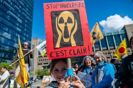 """A little girl is seen holding a placard over her head during the protest. On the day that commemorates the 33rd anniversary of the Chernobyl nuclear disaster, a protest was organized by the """"Fin du nucléaire"""" and Réveil Anti-Nucléaire"""" associations, as well as director Bouli Lanners. They want the five most dangerous Belgian reactors to be shut down."""