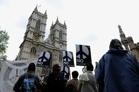 """Activists are seen holding placards during the protest. Anti-nuclear activists gathered opposite Westminster Abbey in London to protest against a service of thanksgiving organised by The Royal Navy to mark 50 years of Britain's submarine-based nuclear weapons. Anti-nuclear activists performed a """"die-in"""" outside Westminster Abbey representing the victims of nuclear war."""