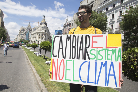"""A demonstrator seen holding a placard that says Change the system, not the climate during the protest. Hundreds of young Spaniards joined the international movement Fridays for Future in Madrid to protest against the climate situation and demand for measures against climate change with the principal slogan """"There is not planet B""""."""