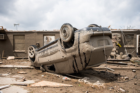 A car is seen flipped over after a tornado struck the area the night before. At least 1 person is dead and 12 injured from the storms that hit western Ohio.