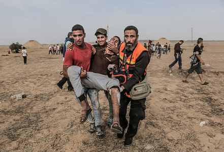 Medical workers carry a wounded person during the clashes. Palestinians clashed with Israeli forces during a major demonstration on the Gaza border demanding for the right to return to their homes at the border fence between Israel and Gaza in the southern Gaza Strip.