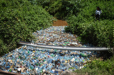 A young woman stands next to Njoro River clogged with thousands of plastic bottles among other kinds of trash. The River that empties its contents into Lake Nakuru, a UNESCO world heritage site carries tons of trash mostly plastic from human settlements. A report says that by 2050 the oceans will have more plastic than fish.