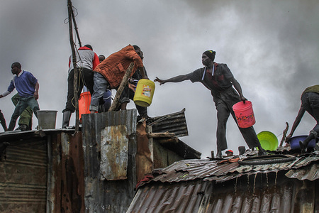 Men use buckets and jerry cans full of water to help put out fire in Kibera Slums. Residents of Kibera Slums were hit by another fire breakout that lead to loss and destruction of properties leaving over 50 residents with no homes. The fire that occurred around 8:00 am in the morning till 10:00 am was caused by poor electric and power connections running through the houses across the neighbourhood. Few residents were left with slight injuries from the struggles in putting out the fire.