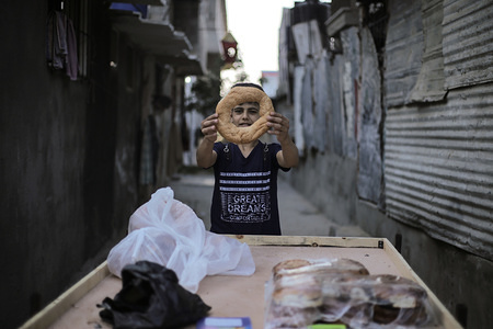 A Palestinian boy shows the donuts, he sells on his cart in the alleys of Khan Yunis refugee camp to get money for his family as the annual unemployment rate in Gaza, southern Gaza Strip.