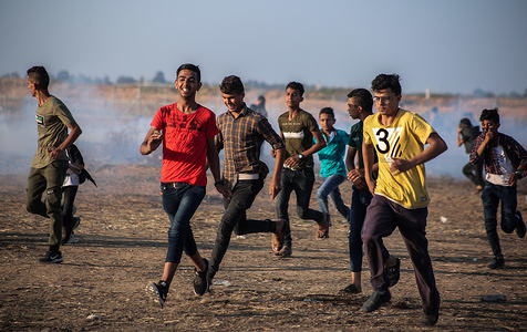 Palestinian demonstrators take cover from tear gas smoke canisters fired at them during the clashes. Palestinians clash with the Israeli forces during a protest calling for lifting the Israeli siege on Gaza and demanding for the right to return to their homeland, at the Israel-Gaza border fence in the southern Gaza Strip.