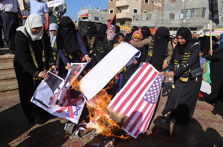 Palestinian women burn placards depicting U.S. President Donald Trump and Israeli Prime Minister Benjamin Netanyahu during a protest against Bahrain's workshop for U.S. peace plan, in southern Gaza Strip.