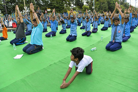 A school student child take part in a mass yoga session on Esplanade, Kolkata to mark the International Day of Yoga.