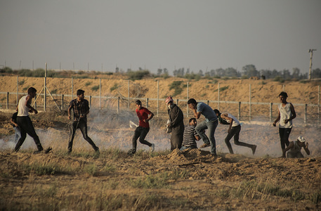 Palestinian protesters flee from tear gas smoke being fired towards them during the clashes. Palestinians clashed with the Israeli forces during a protest calling for the lifting of the Israeli blockade on Gaza and demanding for the right to return to their homeland, at the Israel-Gaza border fence in the southern Gaza Strip.