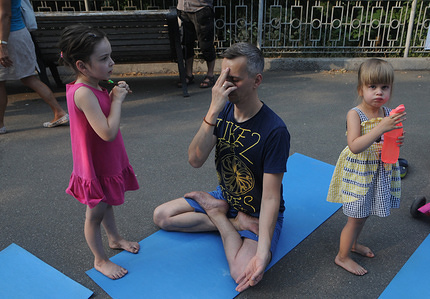 A man with his children seen during a yoga session on the occasion of International Day of Yoga in Kiev.