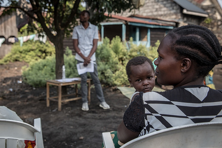 A woman with her kid attend a community meeting aimed at educating locals about the symptoms and treatment of Ebola as part of a community outreach initiative in Goma. DR Congo is currently experiencing the second worst Ebola outbreak in recorded history. More than 1,400 people have died.