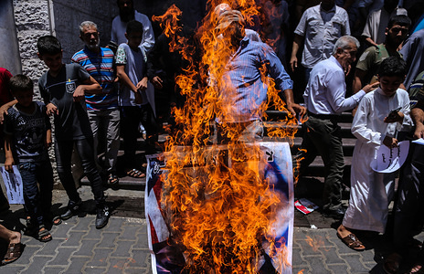 Palestinians burn a poster depicting U.S. President Donald Trump during the protest against Bahrain workshop for US peace plan in Gaza.