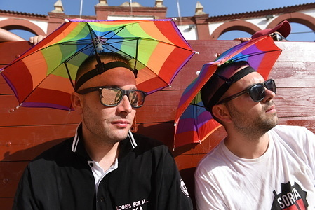 Two men protect themselves from the sun with hat umbrellas as temperatures reached 38º degrees Celsius during the Viernes de Toros celebration in Soria.