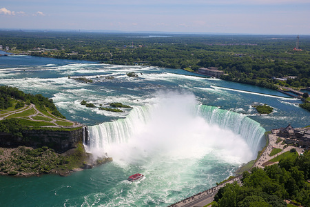 Aerial view of Horseshoe Falls of the Niagara Falls is seen on a hot and sunny day. Niagara Falls is the collective name for three waterfalls - a Horseshoe Fall, an American Falls and a Bridal Veil Falls which is straddle the international border between Canada and the United States; more specifically, between the province of Ontario and the state of New York.