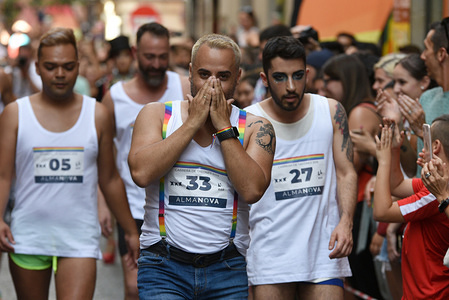 Participants being cheered on during the race. Dozens of costumed men and women take part in the traditional gay pride high heels race in the Chueca district, a popular area for the gay community in Madrid.