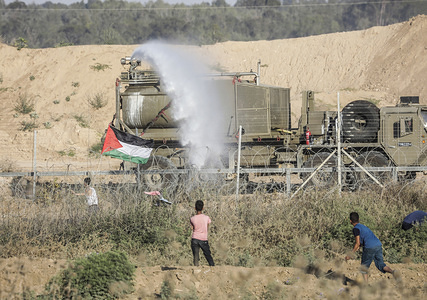 "Israeli forces intervene Palestinian demonstrators with pressurized water during clashes after the demonstration of the ""Great March of Return"" at Israel-Gaza border near Al Bureij Refugee Camp in Gaza City, Gaza."