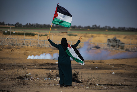 A Palestinian woman waves the Palestinian flag to the Israeli security forces during a demonstration calling for an end to the siege imposed on the Gaza Strip in the southern Gaza Strip.
