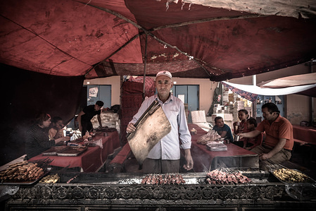 "An ethic Uyghur man cooking Kebab in Kashgar bazaar. The Xinjiang province is located in the North Western part of China, it is the largest province in China. Majority of the population are Muslim in Xinjiang. Recently the Chinese government has enforced a massive security crackdown in Xinjiang, where more than one million ethnic Uyghurs and other mostly Muslim minorities are believed to be held in a network of internment camps that Beijing describes as ""vocational education centres"" aimed at steering people away from religious extremism."