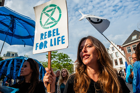 A woman holds a placard that says rebel for life while shouting slogans during the protest. Around thirty people and activists gathered at the town hall in the Dutch city of Utrecht where some political parties are going to vote over a motion of the PvdD (political party for animals in the Netherlands) to explain and declare a climate emergency in The Netherlands. Outside of the city hall was surrounded by the police, people wearing blue clothes while making noise with different objects, also screaming to declare a Climate Emergency.