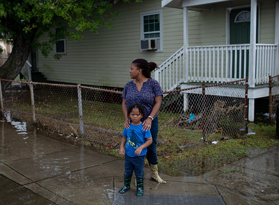 Residents of New Orleans walks through flooded streets following a flash flood that put parts of the city underwater on Wednesday. With the Mississippi River's water level at an all time high and a storm forming in the Gulf of Mexico that is expected to make landfall on the Louisiana and Texas coasts, many fear that levees will fail and that New Orleans will again be inundated as bad as it was in the 2004 aftermath of Hurricane Kartina.