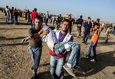 A Palestinian medic carries a wounded person during Clashes while demonstrating demanding an end to the Israeli blockade of Gaza and demanding the right of return to their homes at the border fence between Israel and Gaza in the southern Gaza Strip.