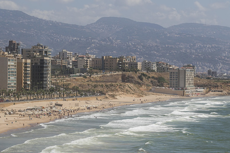 A view of a crowded beach, South Beirut and the mountain ranges on a hot summer day.