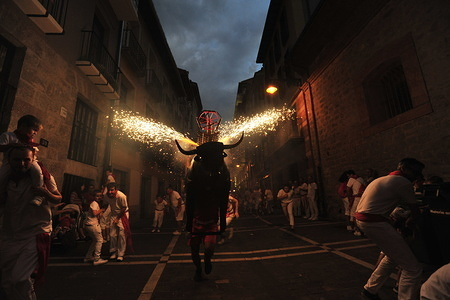 A man runs through the streets with a bull's head and horns that shoot out sparks in all directions during the San Fermin bull running fiesta in Pamplona.  The 'Toro de Fuego' is a typical sight every night during the San Fermin fiesta.