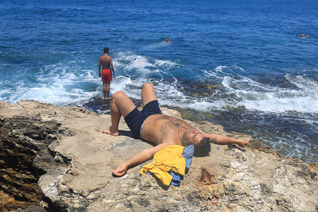 A man gets a sunbath on the rocks at Beirut seafront during a sweltering summer day in the Lebanese capital.