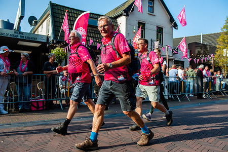 Three men wearing the official t-shirt in pink during the event. Since it is the world's biggest multi-day walking event, the Four Days March is seen as the prime example of sportsmanship and international bonding between military servicemen and women and civilians from many different countries. On the second day, the 'Roze Woensdag' was celebrated, that means that the dress code for the day was pink. Many of the participants dressed in pink to show their support to the LGBTI community. The end of the route is a huge party organized by pink or gay minded cafés.
