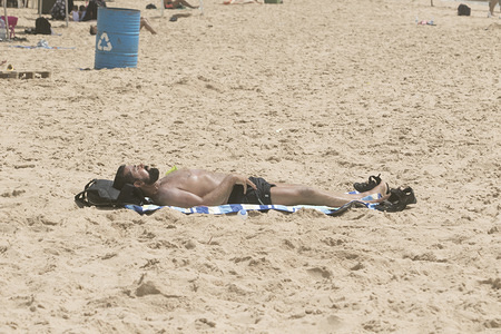 A man sunbathes at the  beach in Beirut during a sweltering day as temperatures exceed 40 degrees Celsius.