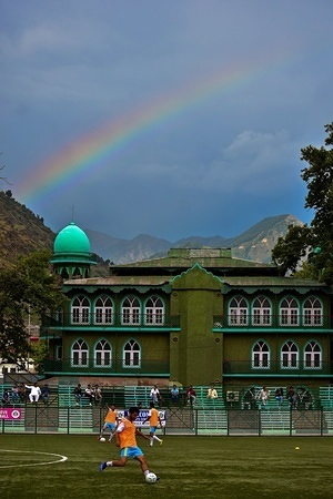 A rainbow is seen as players warm up during a football match in Srinagar, the summer capital of J&K, India.