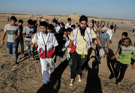 Palestinian medics carry a wounded person during Clashes while demonstrating demanding an end to the Israeli blockade of Gaza and demanding the right of return to their homes at the border fence between Israel and Gaza in the southern Gaza Strip.