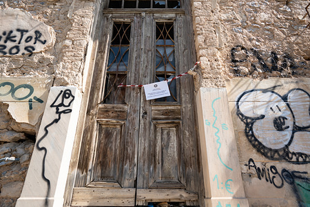 A police sign is seen in front of a derelict building warning people of the danger of entering inside. They attached signs to old buildings following the reported collapse of a building after an earthquake of magniture 5.3 shakes Athens on Friday.