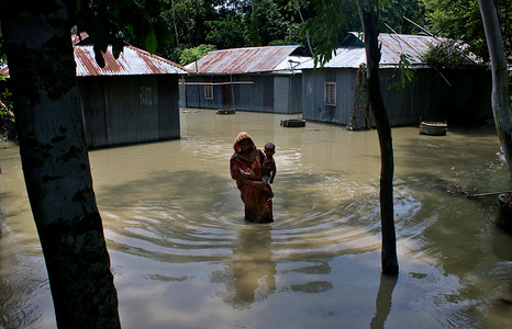 A woman carrying a kid walks in a flood affected area following heavy monsoon rains at a flood affected area in Tangail. Over million people have been affected by floods triggered by the monsoon rains and overflowing river in north, north-eastern and hilly regions in Bangladesh.